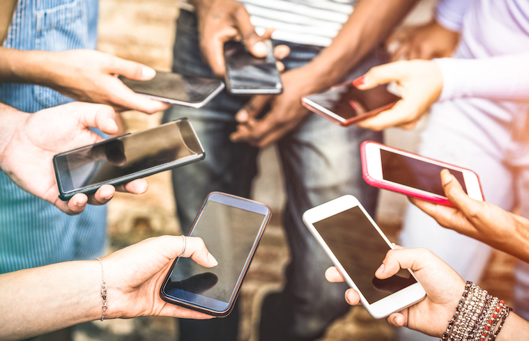 Seven cell phones held by people in a circle